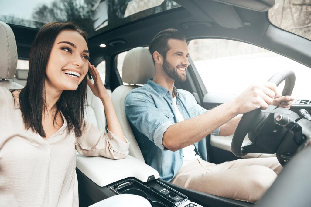 um amn dirigindo e uma mulher sentada no lado do passageiro